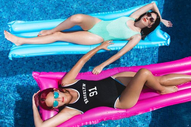 Ženy v celých plavkách a slnečných okuliaroch ležia na nafukovačkách v bazéne