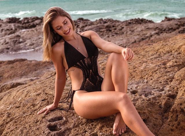 Žena v čiernych plavkách sedí na skale a obdivuje svoje nohy