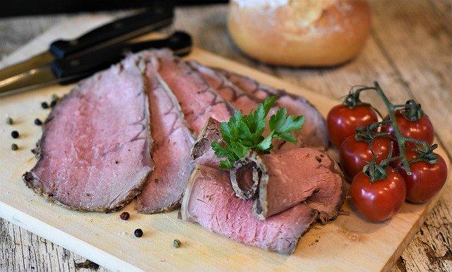 Plátky mäsa a paradajky na drevenom denku.jpg